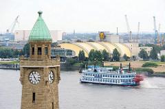 Uhrenturm der St. Pauli Landungsbrücken - ein Raddampfer der Hamburger Hafenrundfahrt fährt elbaufwärts, dahinter das Musicalzelt vom König der Löwen.