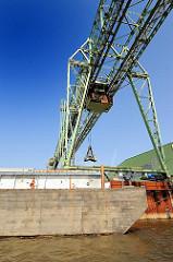 Krananlage am Ufer des Müggenburger Kanals - eine Schute hat am Kai festgemacht - der Ausleger des Krans ragt über das Lastschiff hinaus. Bilder aus dem Industrieviertel Hamburg Veddel.