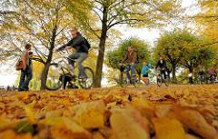 Herbst an der Alster - Herbstlaub auf dem Weg; Radfahrer und Spaziergänger.