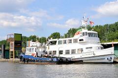 Die alte Hafenfähre Reeperbahn wird als Ausflugsdampfer genutzt - im Hintergrund Bäume des Entenwerder Elbparks in Hamburg Rothenburgort.