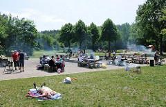 Grillplatz Sandkuhle in Hamburg Rissen - der Platz ist gut besucht - Rauch steigt von den Grills auf; Menschen essen an den Tischen, andere sonnen sich auf der Wiese.