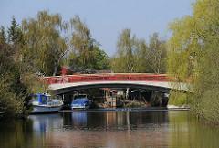 Rote Bruecke über die Bille in Hamburg Billbrook - Sportboote und Motorboote am Ufer des Hamburger Flusses.