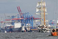 Schiffsverkehr auf der Elbe - Segelschiffe im Hafen Hamburgs - Containerbrücken Terminal Burchardkai.