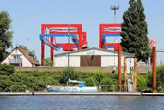 Sportboot am Schlengel im Dradenauhafen - im Hintergrund Containeranlagen des Waltershofer Hafens.