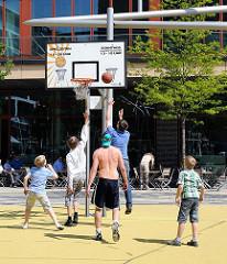 Basketballspiel in der Sonne - Jugendliche auf dem Spielfeld in der Hafencity Hamburgs.