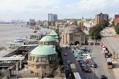 Blick über die Kupferdächer der St. Pauli Landungsbrücken und Gebäude des alten Elbtunnels. Parkplätze für Autos und Reisebusse.