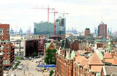 Dächer der Hamburger Speicherstadt am Sandtorkai - Baukräne an der Elbphilharmonie - Stadtteil Hamburg Hafencity.