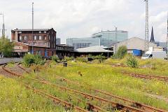 Bahngleise mit blühendem Wildkraut - Lagergebäude, Ziegelbau und moderne Architektur des Spiegelgebäudes in der Hafencity Hamburg.