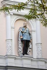 Bauschmuck mit Säulen - Gründerzeitarchitektur, farbig gefasste Skulptur mit Backenbart.