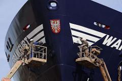 Werften auf Hamburg Steinwerder - Werftarbeiter streichen den Bug eines Schiffsneubaus.
