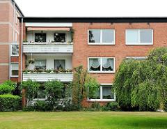 Wohnblock mit Ziegelfassade im Architekturstil der 1960er Jahre - Balkons mit Pflanzen, Gardinen im Fenster.