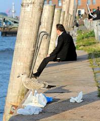Ruhe auf der Kaimauer abseits des Trubel auf dem Fischmarkt Hamburg Altona - eine Möwe hat sich am Abfall sattgefressen.