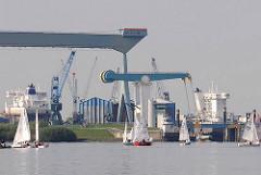 Segelschiffe vorm Estesperrwerk - Portalkran und Schiffsneubau der Sietas Werft.