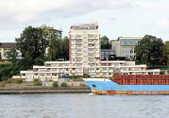 Der Frachter Rebecca Rousing fährt mit geöffneten Ladeklappen auf der Elbe vor Wedel - am Ufer die Seniorenresidenz Graf Luckner.