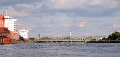 Blick von der Norderelbe zu den Freihafenelbbrücken - zwei Schiffe haben an den Dalben in der Mitte des Hamburger Stroms festgemacht. Hinter den Elbbrücken der Turm der Wasserwerke und dem Heizkraftwerk Tiefstack.