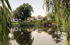 Einzelhäuser / Alstergrundstücke am Ufer vom Alsterkanal; Weidenzweige - Kanu auf dem Fluss.