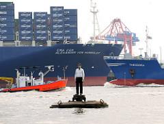 """Skulptur """"Mann auf Boje"""" Elbe, Hamburger Hafen - Künstler Stephan Balkenhol - im Hintergrund der Containerfrachter CMA CGM ALEXANDER VON HUMBOLDT sowie der Bug von einem Tankschiff und Containerfeeder."""