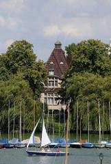 Blick durch die Masten der am Steg liegenden Boote zu einer Villa mit Alsterblick, die zwischen hohen Bäumen an der Bellevue steht.