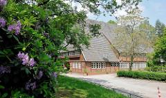 Bauernhaus mit Biergarten im Altonaer Volkspark / Stadtteil Hamburg Bahrenfeld; blühende Rhododendron.