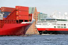 Schiffsbegnungen auf der Elbe - vor Hamburg Altona; ein Kreuzfahrtschiff läuft aus, ein roter Containerfeeder kommt im Hamburger Hafen an.