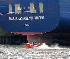 Heck des Containerschiffs CMA CGM ALEXANDER VON HUMBOLDT - kleines Motorboot in Fahrt, Gischt.