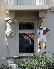 Stützende Figur eines Gründerzeit-Wohngebäudes - Spielerfigur im Trikot der Mannschaft FC St. Pauli
