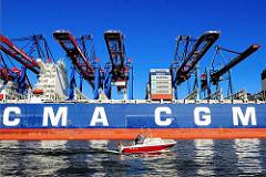 Der Containerfrachter CMA CGM Christophe Colomb liegt am Terminal Burchardkai unter den Containerbrücken - ein Sportboot fährt durch den Waltershofer Hafen.