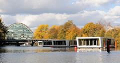 Hochwasserbassin Hamburg Hammerbrook -  Schwimmende Häuser, Hausboote - wohnen auf dem Wasser. Im Hintergrund das Bürogebäude Berliner Bogen; Herbstbäume.