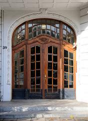 Hauseingang im  Gründerzeitstil - verglaste Holztür mit Schnitzereien und Oberlicht.