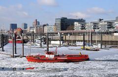 Feuerlöschboot beim eisbedeckten Sportboothafen in der Hamburger Neustadt - das Löschboot wird als Eisbrecher eingesetzt.
