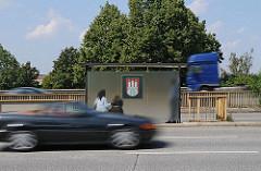 Bushaltestelle mit Hamburg-Wappen auf der Veddel - rasende Autos auf der Strasse.