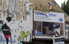 neubauwohnungen zu verkaufen - graffiti an einem abrisshaus - schild neubauwohnungen zu verkaufen.