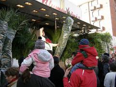 Verkauf von Grünpflanzen - Palmen auf dem Fischmarkt. Marktbesucher tragen ihre Kinder auf der Schulter.