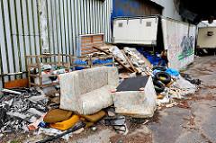 Wild abgeladener Müll am Strassenrand von Hamburg Wilhelmsburg - Couchgarnitur und Müllsäcke im aufgebrochenen Container.