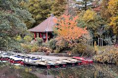 Blick auf die Liebesinsel im Herbst - Tretboote und Ruderboote am Bootssteg - Bäume und Sträucher in Herbstfarben.