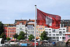 Hamburg Flagge im Wind an der Elbe - bunte Häuser der St. Pauli Hafenstrasse.