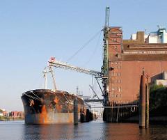 Die Ladung eines Massengutfrachters wird beim Rethespeicher gelöscht - die Sauganlage ragt aus dem Speichergebäude - Fotos aus dem Stadtteil Hamburg Wilhelmsburg.