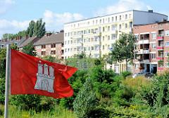 Eine Hamburgflagge weht im Wind - im Hintergrund Wohnblocks im Hamburger Stadtteil Hamm.