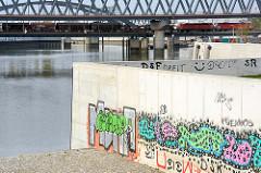 Promenade und Terrasse am Wasser zum Billehafen in Hamburg Rothenburgsort - buntes Graffiti an den neuen Mauern.