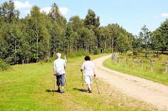 Ein Paar macht Nordic Walking im Naturschutzgebiet Höltingbaum. Freizeitsportmöglichkeiten in Hamburg und im Hamburger Umland.
