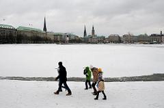 Winter in Hamburg, die Binnenalster ist mit Eis und Schnee bedeckt - eine Familie gehtm am Alsterufer spazieren - im Hintergrund die Hamburger Altstadt.