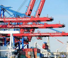 Containerbrücken im Hamburger Hafen - HHLA Container Terminal Tollerort. Ein Container wird an Land transportiert.