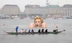 Eine Riesennixe sitzt im Wasser der Hamburger Alster - Kopf und Knie sehen aus dem Wasser heraus - ein Drachenboot hat auf der Binnenalster angehalten, die Ruderer betrachten die ca. 4m hohe Figur aus Styropor