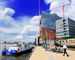 Boot der Wasserschutzpolizei am Anleger Elbphilharmonie - Hafencity Hamburg; Baustelle Elbphilharmonie mit Baukränen.