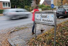 Stadtteilschild an der Strasse, Strassenverkehr und Fussgänger.