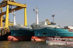 Wulstbug zweier Auflieger - Frachtschiffe im Steinwerder Ellerholzhafen - Fahrgastschiff der Hafenrundfahrt in voller Fahrt.