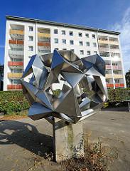Kunst im öffentlichen Raum - abstrakte Metallskulptur vor einem Hochhaus mit farbigen Balkons.