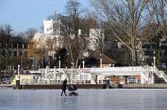 Anleger Rabenstrasse im Winter. Spaziergängerin mit Kinderwagen auf der zugefrorenen Alster.
