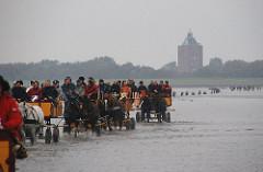 Wattwagen mit Fahrgästen im Watt vor der Insel Neuwerk - diesiges Wetter, Leuchtturm in Hintergrund.