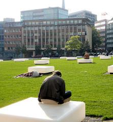 Grünanlage, Rasenfäche am Domplatz in der Hamburger Innenstadt - weisse Sitzquader / Bänke, die die 39 Säulen des Mariendoms in der Hamburger Altstadt symbolisieren.